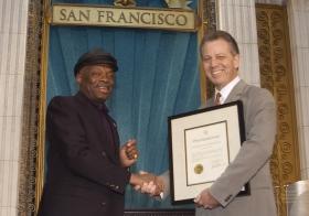 """Para la ocasión, el alcalde de SanFrancisco, Willie Brown (a la izquierda) entregó una proclamación a la Iglesia para encomiarle """"por sus esfuerzos en lograr que Bay Area sea un lugar mejor para las personas de todas las razas, colores, credos y de todo nivel social""""."""